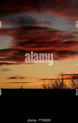 Sunset with hunter hide on horizon. Evening picture with beautiful red sky, trees and hide on the background. - Stock Photo