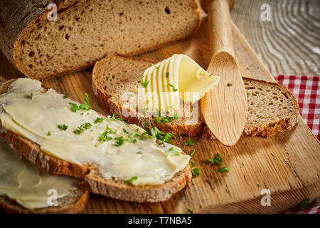 Buttered slices of fresh rye bread topped with chopped parsley and a decorative twist or curl of butter on a wooden board with spreader or butter knif - Stock Photo
