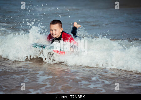 Little boy playing in the surf with a bodyboard. - Stock Photo