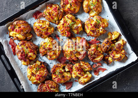 Australian Crash Hot  new Potatoes sprinkled with spice, fried bacon and herbs  on a sheet pan on a concrete table, view from above, flatlay, copy spa - Stock Photo