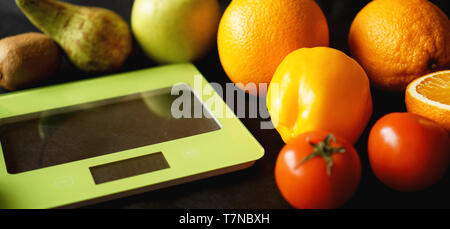 Concept diet. Healthy food, kitchen weight scale. Vegetables and fruits. Top view close-up on black background - Stock Photo