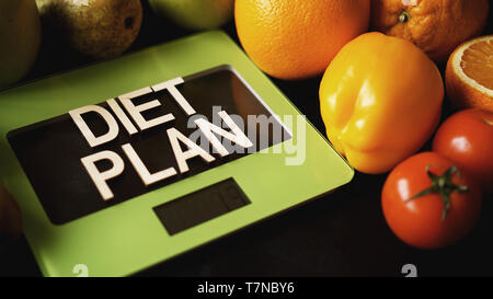 Concept diet. Healthy food, kitchen weight scale. Vegetables and fruits lettering Diet plan on black background - Stock Photo