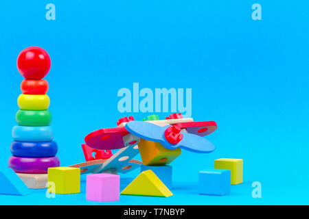 Baby kid toy background. Wooden toy plane, baby stacking rings pyramid and colorful blocks on blue background - Stock Photo
