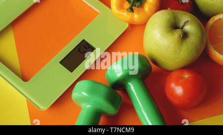 Concept diet. Healthy food, kitchen weight scale. Vegetables and fruits. Top view close-up on orange background - Stock Photo