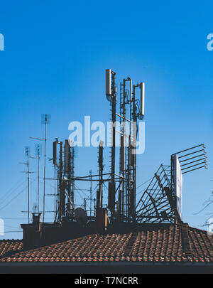 Wide shot of different aerial antennas for radio television and mobile transmission on roof tile building against blue sky - Stock Photo
