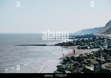 Sheringham, UK - April 21, 2019: People with dogs enjoying sunny day on a beach in Sheringham. Sheringham is an English seaside town within the county Stock Photo