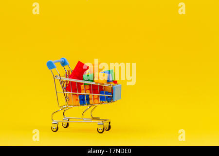 Shopping trolley cart full of colorful bricks on yellow background - Stock Photo