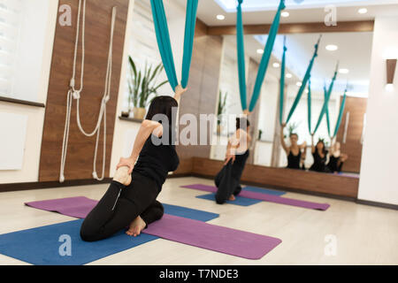 Woman doing fly yoga stretching exercises in gym. Fit and wellness lifestyle. - Stock Photo