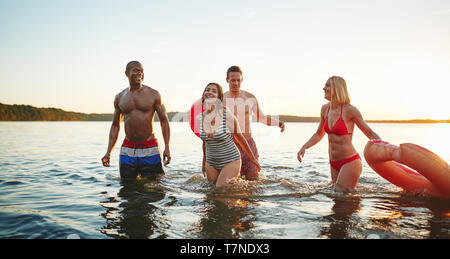Group of diverse young friends wearing swimsuits laughing while walking together in a lake on a late summer afternon - Stock Photo