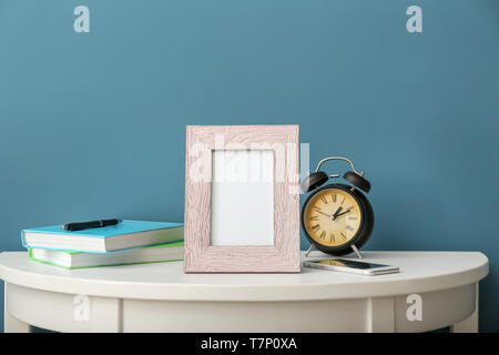 Composition with photo frame on white table against color background - Stock Photo