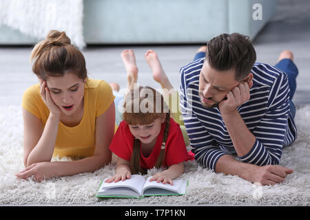 Parents and their daughter reading book together at home - Stock Photo