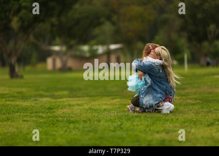 Baby hugging with mom in the park on the green grass - Stock Photo