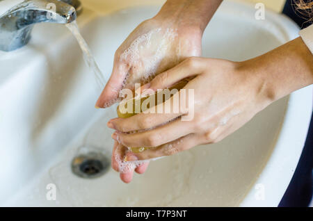 Woman washing hands with hypoallergenic soap at home - Stock Photo