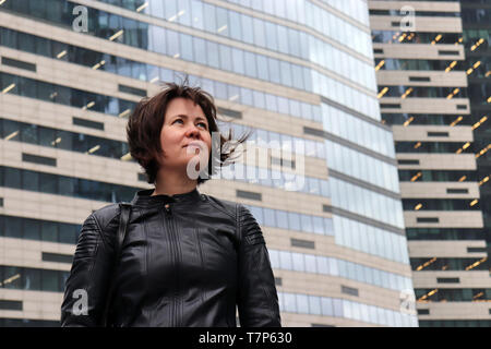 Inspired woman on futuristic city background, glimpse at future. Portrait of happy girl with flowing hair in black leather jacket against a skyscraper - Stock Photo