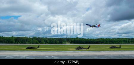 A commercial plane flying Georgia Army National Guardsmen from the Marietta based 1st Battalion, 171st Aviation Regiment, takes of while UH-60 Black Hawks from the unit prepare for takeoff from the Clay National Guard Center, Marietta, Ga., on May 5, 2019.  The Guardsmen are conducting post-mobilization training prior to deployment to Kosovo in support of peacekeeping operations in the area.    U.S. Army National Guard photo by Sgt. 1st Class R.J. Lannom Jr - Stock Photo