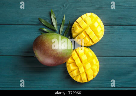 Cut ripe mangoes and palm leaf on wooden background, space for text - Stock Photo