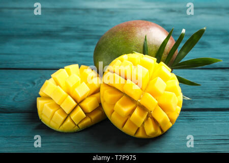 Cut ripe mangoes and palm leaf on wooden background, closeup - Stock Photo
