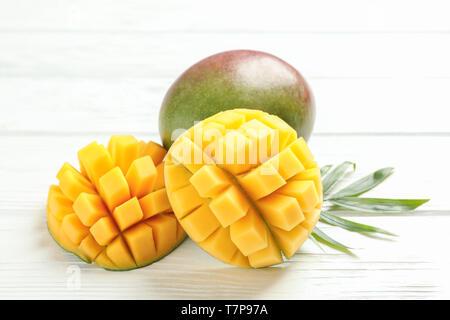 Cut ripe mangoes and palm leaf on white background, closeup - Stock Photo