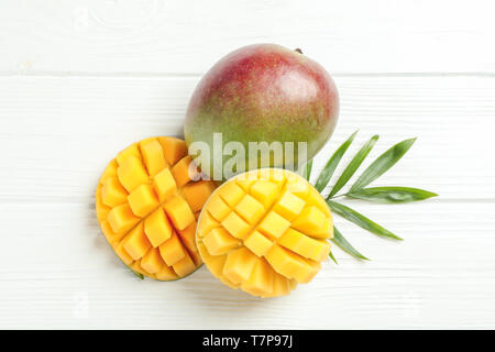 Cut ripe mangoes and palm leaf on white background, space for text - Stock Photo