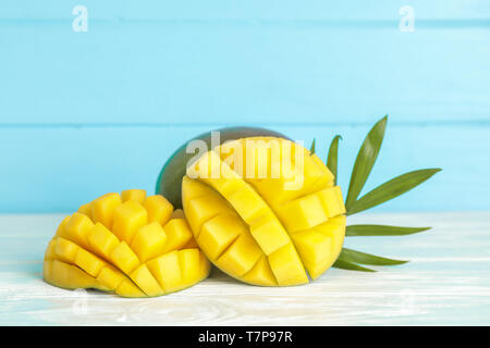 Cut ripe mangoes and palm leaf on white table against color background, space for text - Stock Photo