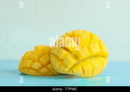 Cut ripe mangoes on color table against white background, closeup - Stock Photo