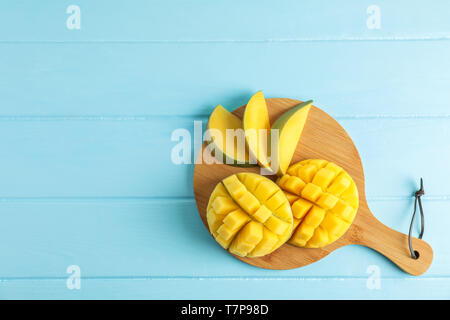 Cutting board with cut ripe mangoes on color background, top view - Stock Photo
