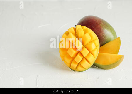 Cut ripe mangoes and space for text on white background, closeup - Stock Photo