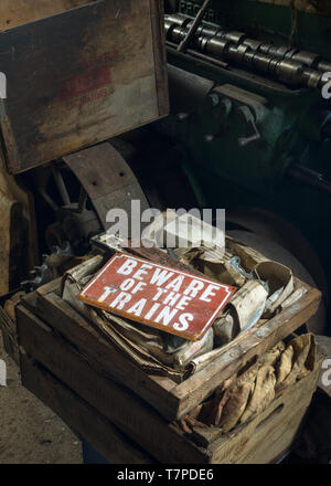 A vintage, red 'Beware of the Trains' sign lying unused in a train engineers workshop, the Mining Museum, Lake District, UK - Stock Photo