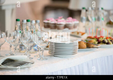Buffet table with dishes and snacks.A stack of white plates on the table of the buffet table - Stock Photo