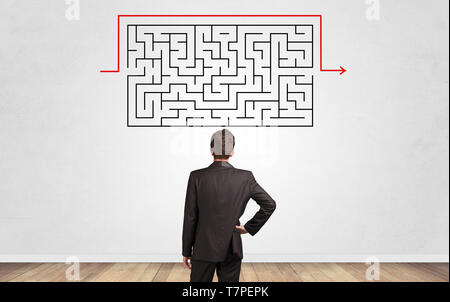 Businessman in doubt looking to a maze and searching the way out - Stock Photo
