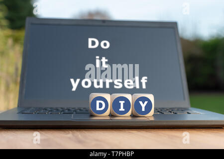 Dice form the abbreviation 'DIY'. Dice placed on a Notebook. The text 'Do it Yourself' is written on the display. - Stock Photo