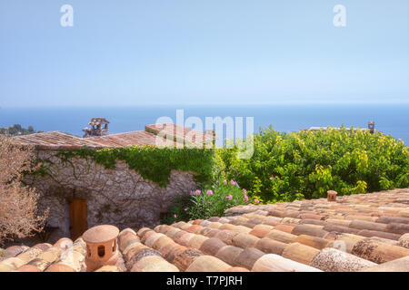 view on the Mediterranean Sea over the roofs of the picturesque medieval village of Eze in France - Stock Photo