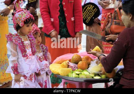 MANDALAY, MYANMAR - DECEMBER 18. 2015: Cute Burmese girl choosing fruits during ceremony at Maha Muni Pagoda - Stock Photo