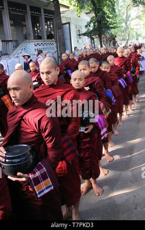 MANDALAY, MYANMAR - DECEMBER 18. 2015: Procession of Buddhist monks at Mahagandayon Monastery in the early morning - Stock Photo