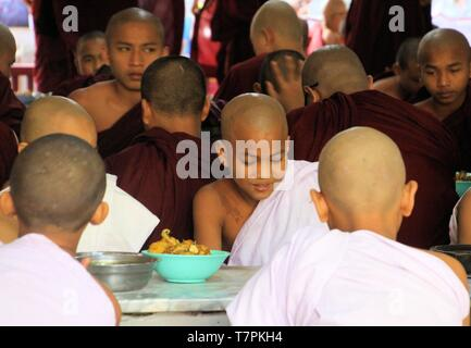 MANDALAY, MYANMAR - DECEMBER 18. 2015: Buddhist monks having breakfast at Mahagandayon Monastery - Stock Photo