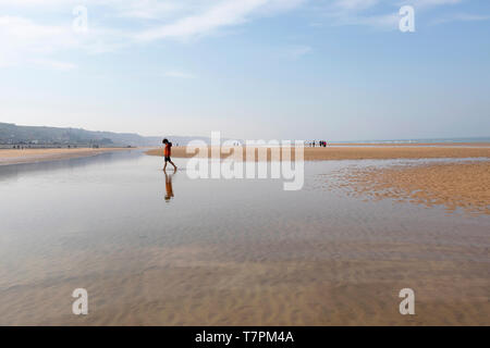 Young boy walking on sand at Omaha Beach, one of the D-Day beaches of Normandy, France - Stock Photo