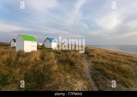 Path at a row of beach Huts with colorful roofs on a grass covered dune and beautiful view over the atlantic ocean, Gouville-sur-Mer, Normandy, France