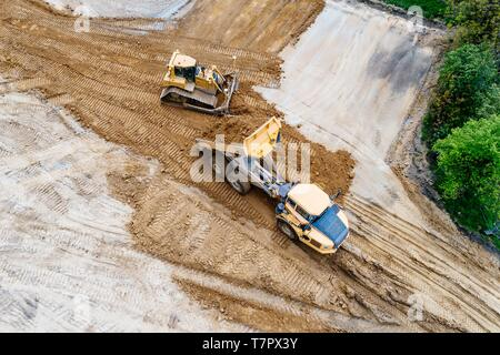 Aerial drone view on bulldozer and dumper truck working on building site. Road construction - Stock Photo