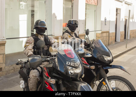 Two members of the special Delta police force sitting on their high powered motorbikes in a side street in Sucre Bolivia, both wearing masks - Stock Photo