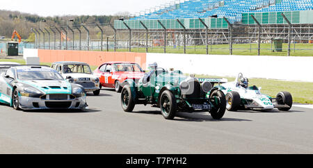 Historic Race Cars from Different eras, and different types, on a parade lap, during the 2019 Silverstone Classic Media Day. - Stock Photo