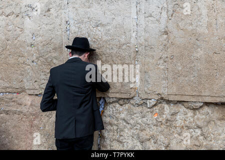 Jerusalem,israel,27-march-2019: Jewish man prays next to a crack filled with letters containing written prayers at the Western Wall in Jerusalem. Isra - Stock Photo