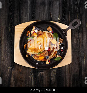 Delicious sweet pancakes served on a cooking pan with fresh fruits, nuts and chocolate sauce - Stock Photo