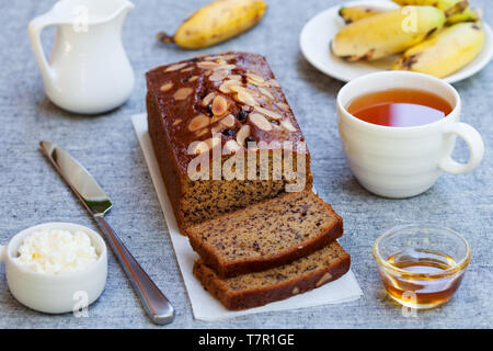 Banana cake, loaf bread with chocolate and cup of tea on grey textile background. - Stock Photo
