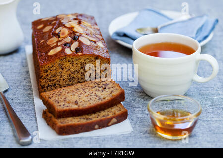 Banana, carrot, apple cake, loaf with chocolate and cup of tea on grey background. - Stock Photo