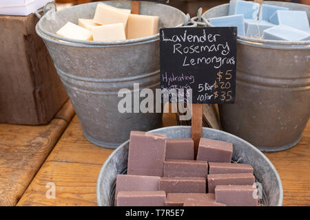 A close up photo of bars of colourful home made soap in large metal pails for sale at a Farmers Market - Stock Photo