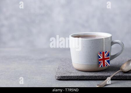 Tea in mug with British flag tea bag label. Grey background. Copy space. - Stock Photo