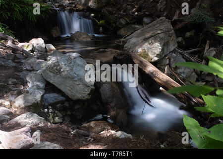 A small multi-tiered waterfall with rocks and green foliage, long exposure shot to smooth out the cascading water - Stock Photo