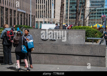 New York, NY - April 3, 2019: Two women are seen talking near the 21st Century Fox cornerstone sign with it's logo at this company's New York headquar - Stock Photo