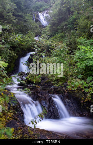 A small multii tiered waterfall just off the side of the road, long exposure shot to smooth out the cascading water - Stock Photo