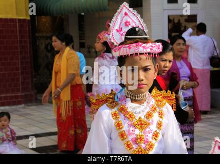 MANDALAY, MYANMAR - DECEMBER 18. 2015: Novitiation (novitiate) ceremony (Shinbyu) for young Buddhist boy with make-up and lipstick at Maha Muni Pagoda - Stock Photo